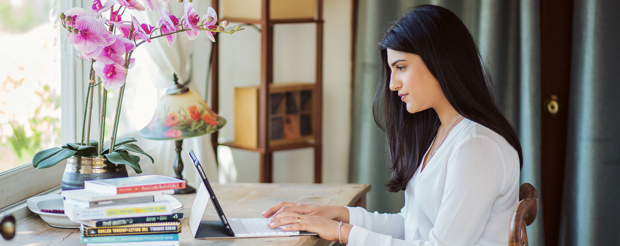 A photo of therapist Sakina Issa working at her computer.