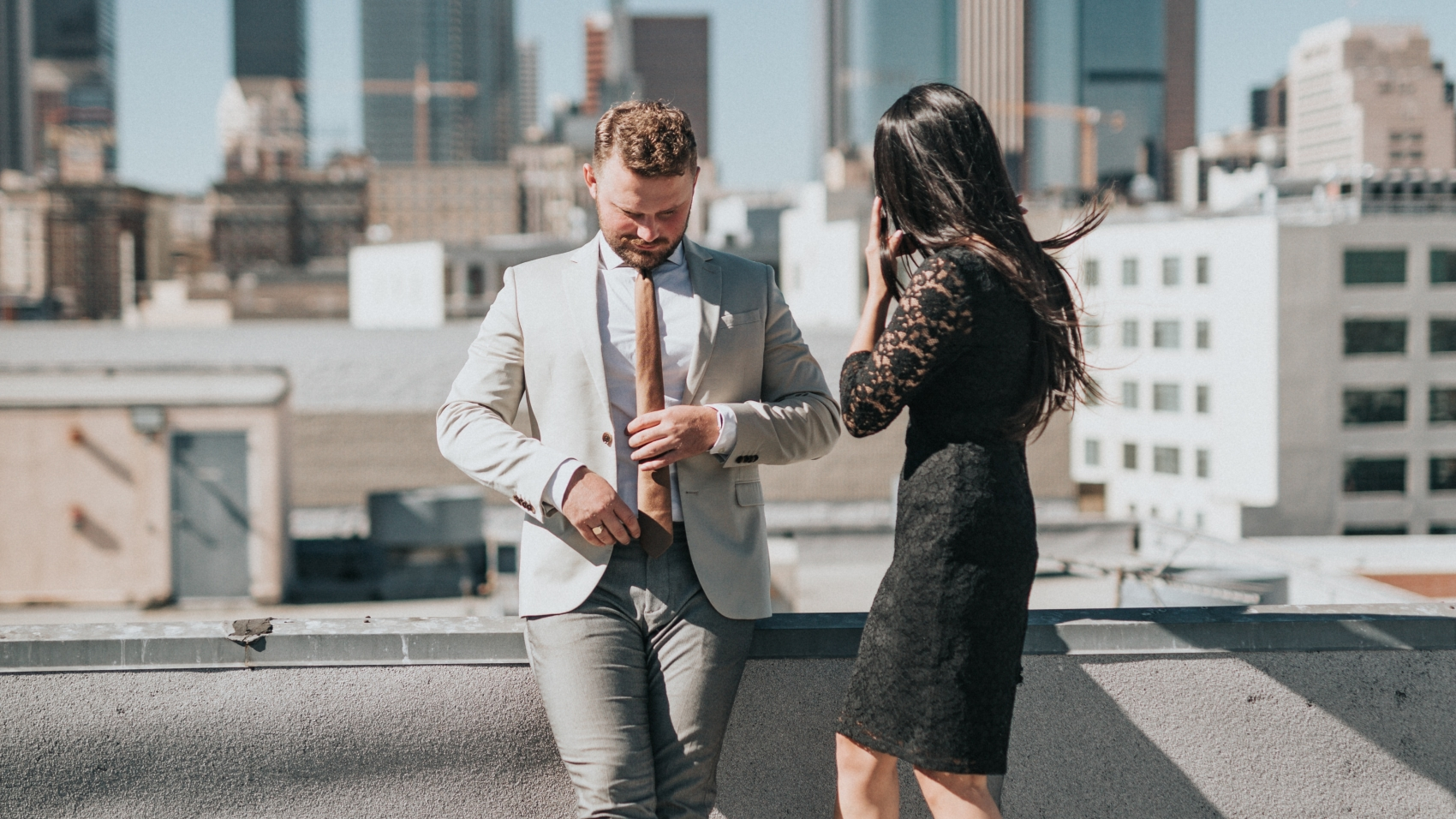 Couple on windy rooftop, he fidgets with his tie, she looks into the distance.