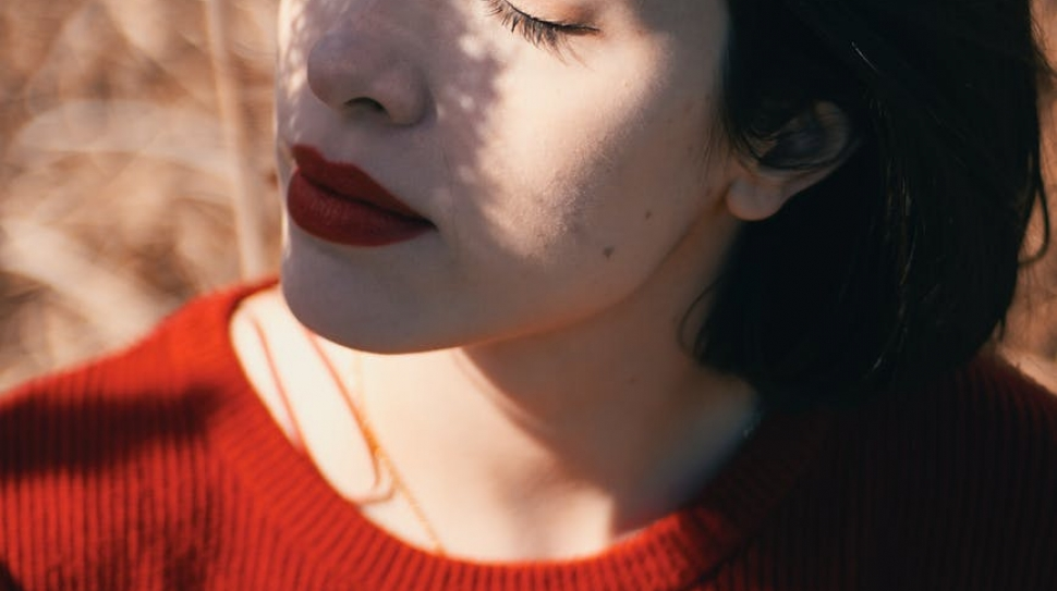 A woman in a red sweater closes her eyes in sunlight. Self-love is warm and comforting like the sun on your skin.