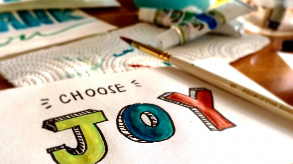 """A painting of the words """"choose joy"""" in bright green, red, and blue."""
