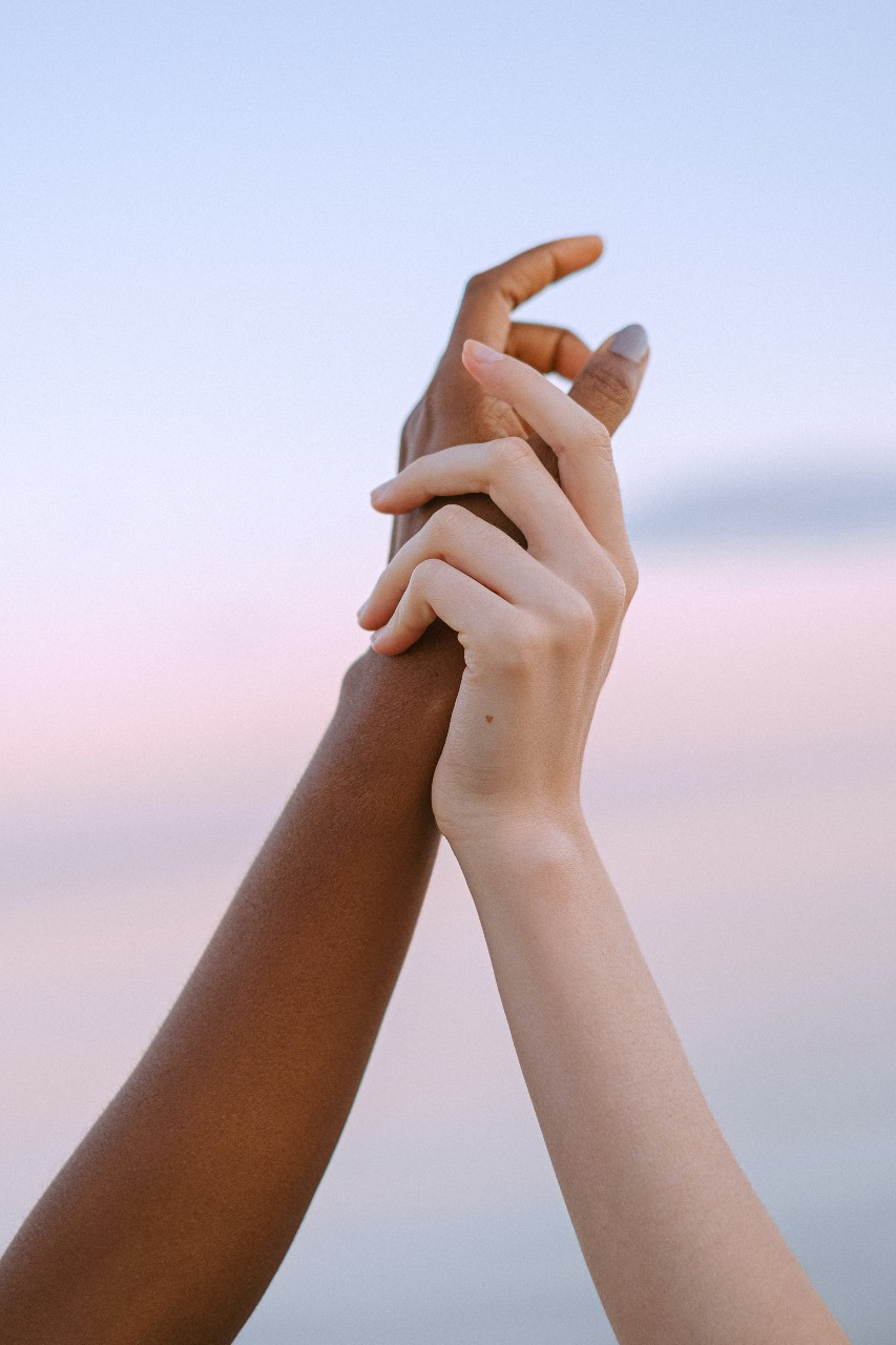 Two hands, one white, one black, are grasped in a show of empathy