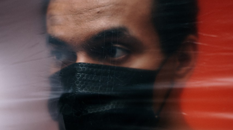 a man in a mask behind a plastic barrier