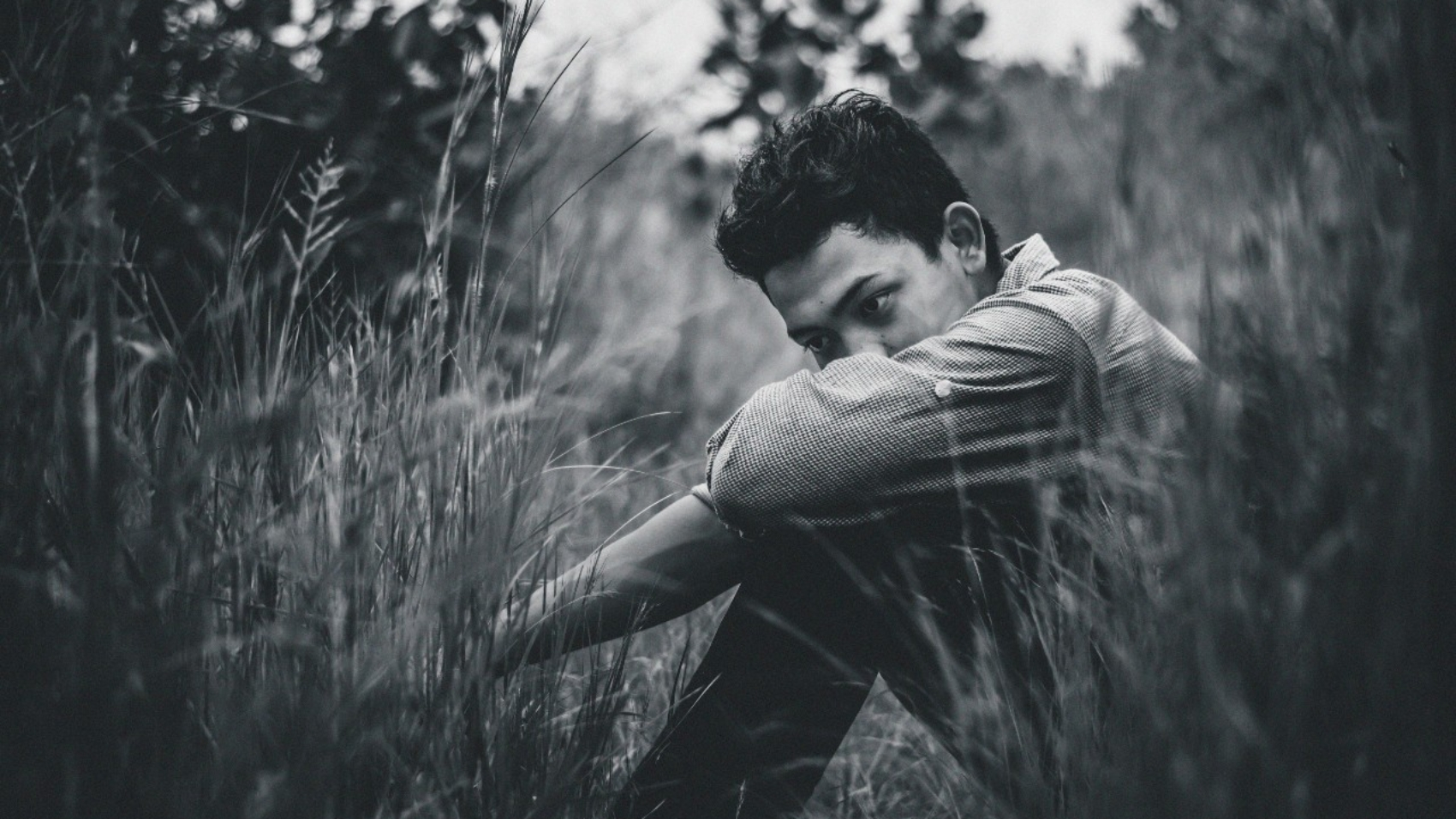 A man sits in a field, lost in thought