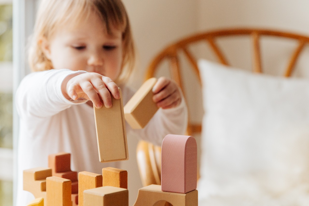 A child concentrates as she stacks blocks