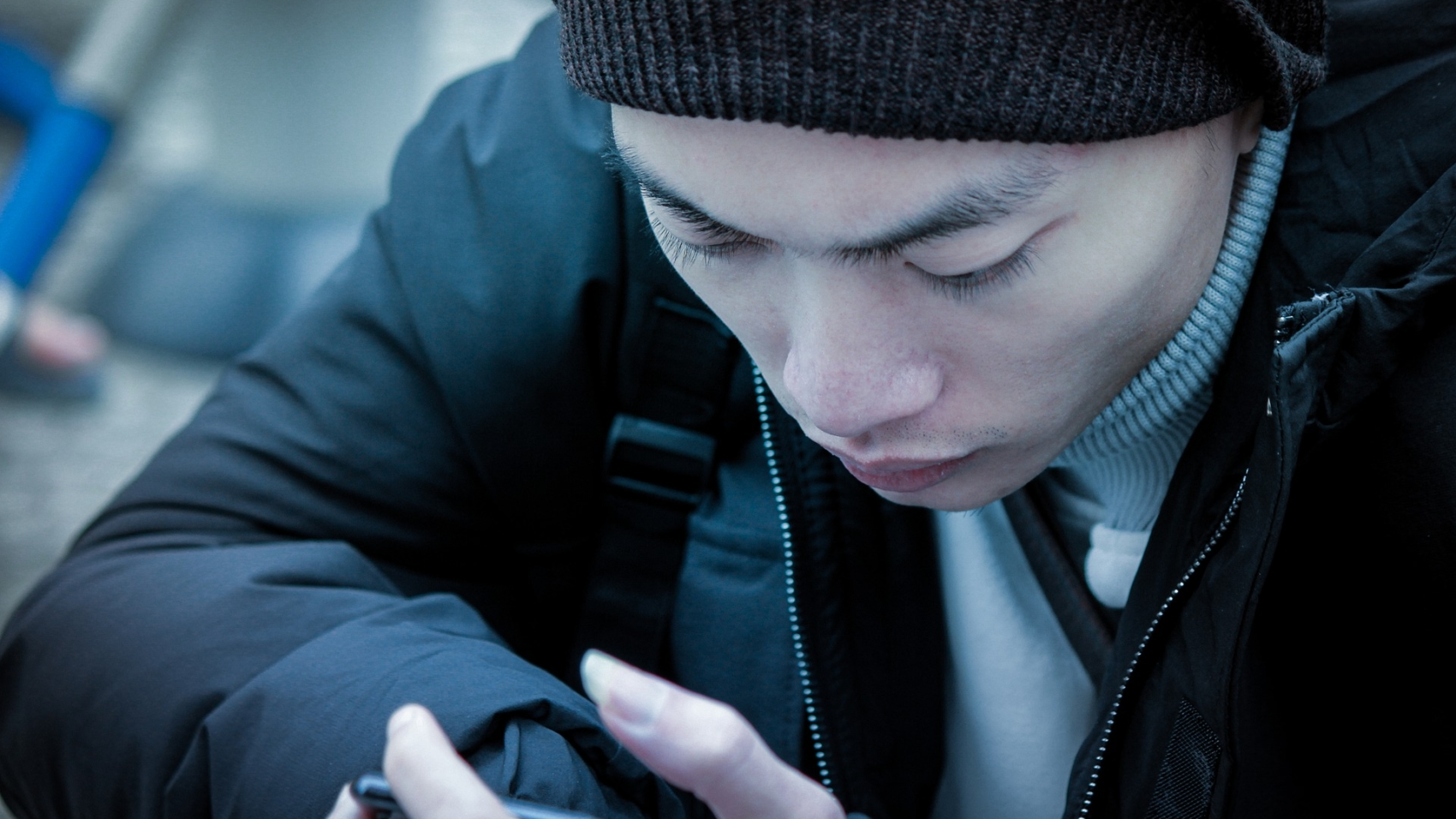 A man looks intently at his smartphone.