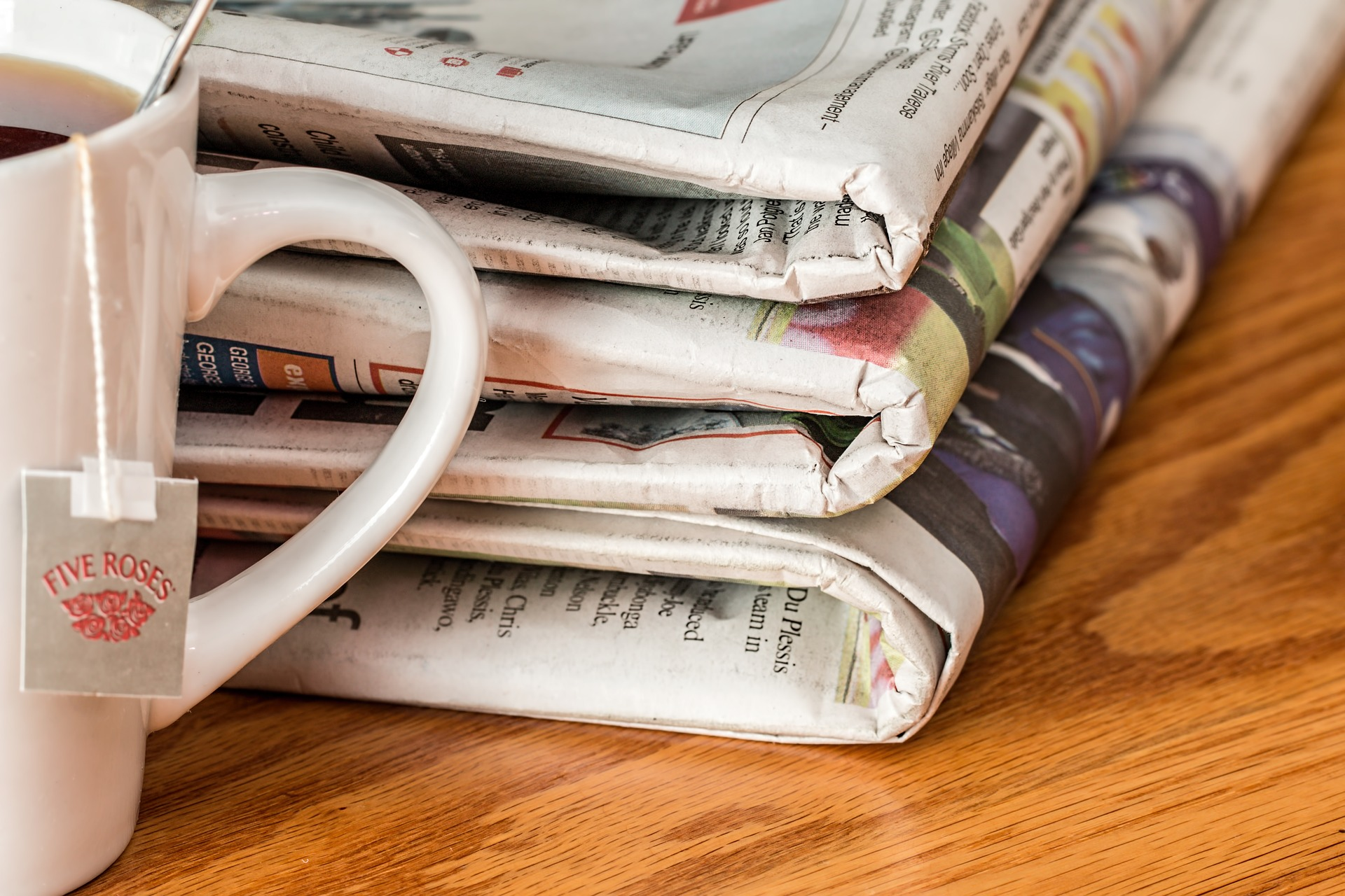 A pile of newspapers sit next to a morning tea cup.