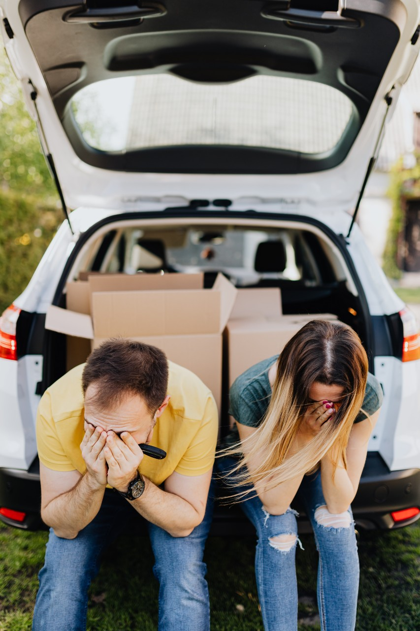 Two adults sit in the back of a car with their hands over their faces. They look tired and frustrated.