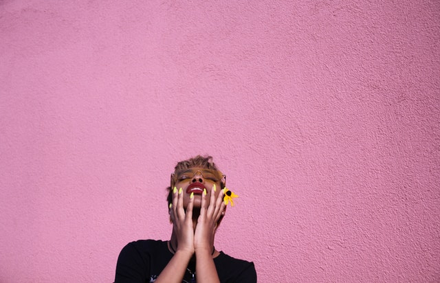 A woman holding a flower looks up, a pink wall behind her.
