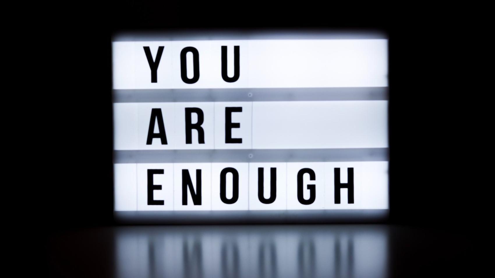 "A sign with the illuminated words ""you are enough"""