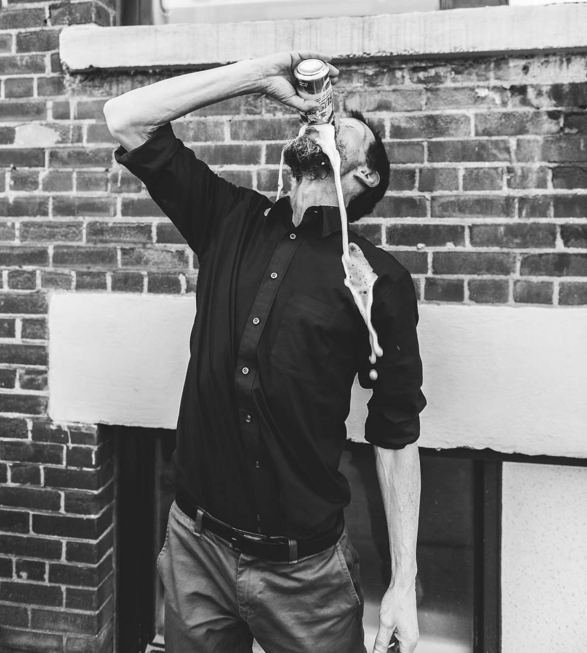 A man tiltin his head back has his drink spilling down his face and shirt.