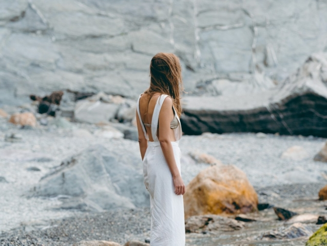 A woman stand alone on a rocky seashore, her face is not visible